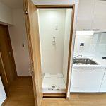 洗濯機置き場は、家事動線を考えてキッチンの横にあります。扉があるので普段は隠せます(内装)